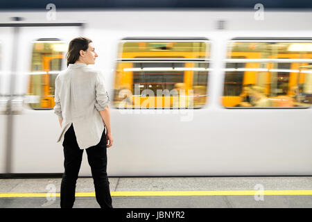 A woman standing on the platform of a U-Bahn (subway) station in Vienna, Austria as a train arrives. - Stock Photo