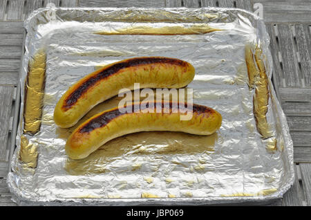 grilled sausages on grill with silver foil, close up, macro, full frame - Stock Photo