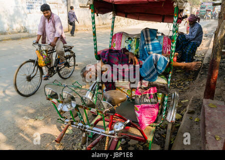 A man is sleeping on his cycle rickshaw on a road in the suburb New Market - Stock Photo