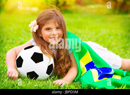 Young cheerful football fan lying down on fresh green grass with ball and big Brazil flag, happy supporter of Brazilian - Stock Photo