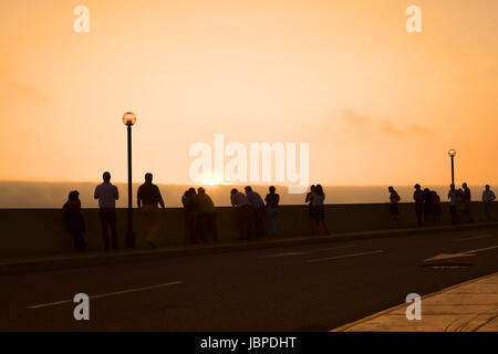 LIMA, PERU - MARCH 11, 2012: Unidentified people watching the sunset over the Pacific ocean from the pavement along - Stock Photo