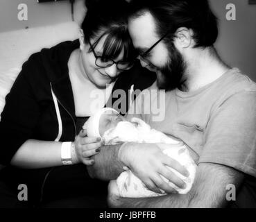 New Mother & Father Hold Their Newborn Daughter at the Hospital - Stock Photo