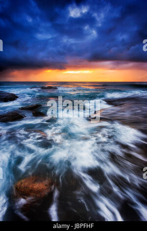 Dark dawn time at Bungan beach of Pacific coast in Sydney, Australia. Strong waves roll on eroded boulders under - Stock Photo