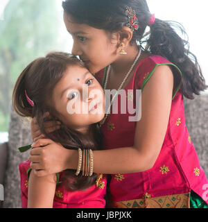 Indian girl kissing her younger sister with love. Asian family at home. Beautiful daughters in traditional India - Stock Photo