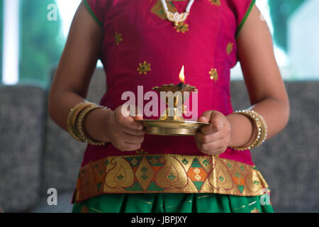 Diwali or deepavali photo with little girl hands holding oil lamp during festival of light. - Stock Photo