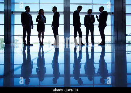 Silhouettes of several office workers standing by the window and working - Stock Photo