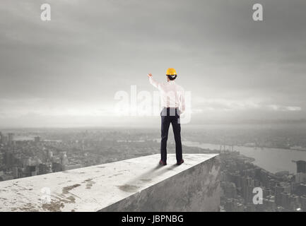 Businessman with helmet indicates the right direction - Stock Photo