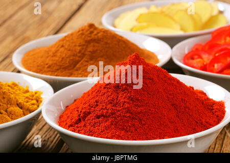 Bowls of curry powder, paprika,  ground cinnamon, sliced ginger root and red pepper - Stock Photo
