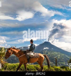 BANOS, ECUADOR - DECEMBER 10: Unrecognizable farmer on a horse looking at the  Tungurahua volcano eruption - december - Stock Photo