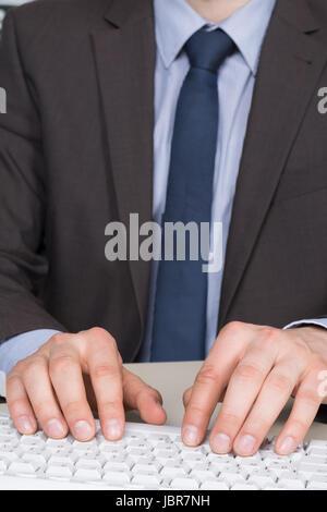 Geschäftsmann im Anzug tippt im Büro auf der Tastatur. - Stock Photo