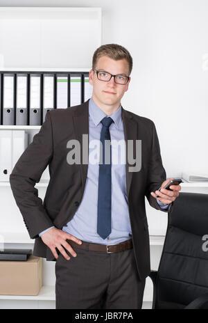 Junger Geschäftsmann mit Brille steht im Büro vor einem Regal und hält dabei in der Hand ein Smartphone. Der Mann schaut zur Kamera.