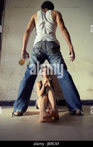 People, substance abuse and domestic violence. Drunk man standing with whiskey bottle and threatening his young - Stock Photo