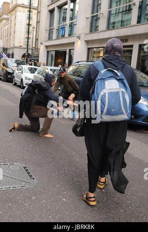 London, UK. 11th June, 2017. Beggars fight in Dover Street Credit: Fabrizio Carta/Alamy Live News - Stock Photo