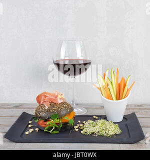Healthy burger with hamon, tomatoes, micro greens and black wholegrain buns, vegetable sticks and red wine on black - Stock Photo
