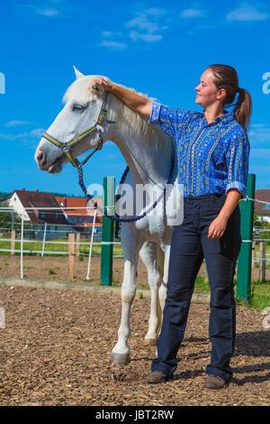 Junge Frau streichelt weisses Pferd - Stock Photo