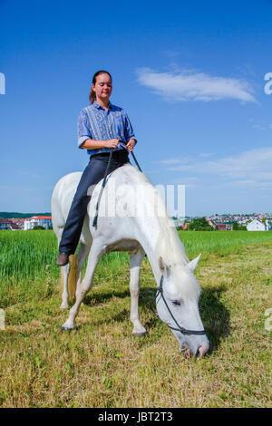 Junge Frau sitzt ohne Sattal auf einem weissem Pferd - Stock Photo