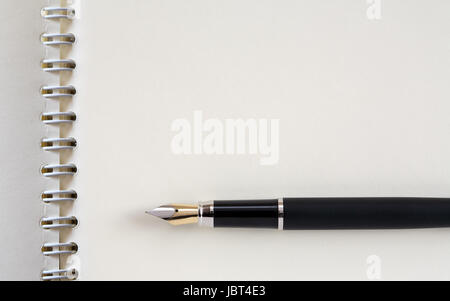 Fountain pen on open spiral notebook. Good background with free space - Stock Photo