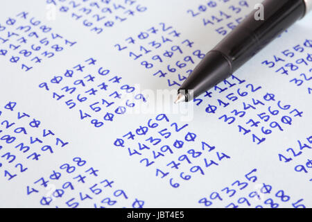 Closeup of bollpoint pen on paper with columns of written numbers - Stock Photo