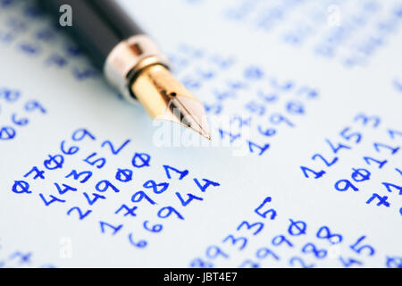 Closeup of fountain pen on paper with columns of written numbers - Stock Photo