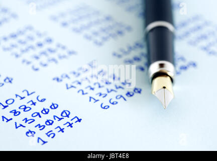 Closeup of fountain pen on paper with written numbers columns - Stock Photo