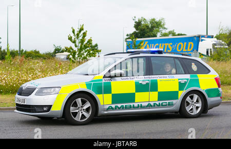 South East Coast Ambulance car speeding on a roundabout with blue lights on in the UK.