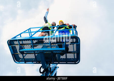 Construction workers on site in hydraulic lifting ramp discussing the project on pad or tablet computer - Stock Photo