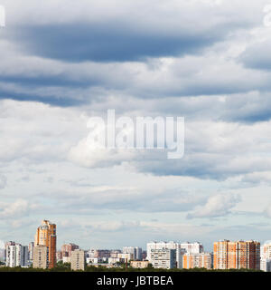 overcast grey sky over town in summer day - Stock Photo