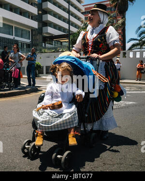 Puerto de la Cruz, Tenerife, Canary Islands - May 30, 2017: A little girl dressed in traditional clothes sits in - Stock Photo