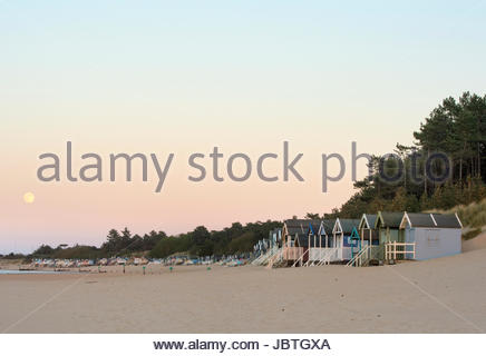 The beach huts at Wells next the Sea on the North Norfolk coast as the sun sets and a full moon rises - Stock Photo