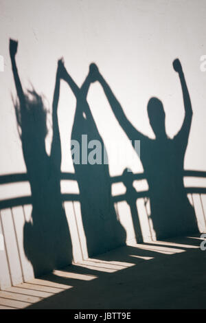 Creative photo of happy people shadows on white wall holding hands - Stock Photo