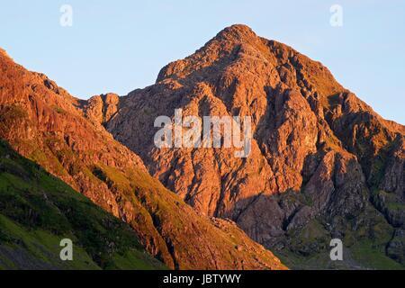 Summer light hits a pinnacle in Bidean Nam Bian in Glencoe - Stock Photo