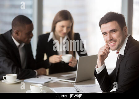 Cheerful businessman wearing suit looking at camera sitting at desk with international partners, experienced team - Stock Photo