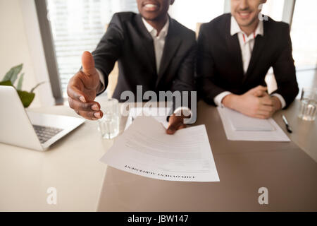Close up of black businessman offering job, reaching out employment agreement to successful applicant, labor contract - Stock Photo