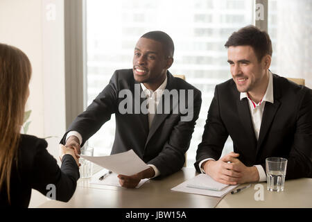 Two cheerful black and white recruiters welcoming female applicant on job interview, african and caucasian hr managers - Stock Photo