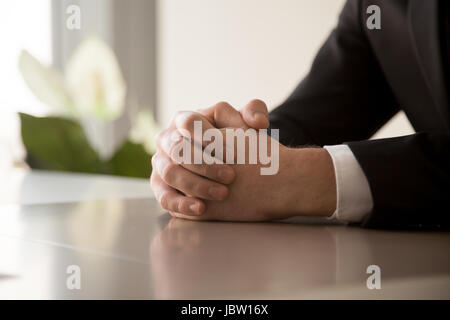 Close up of male clasped hands clenched together on table, businessman preparing for job interview, concentrating - Stock Photo