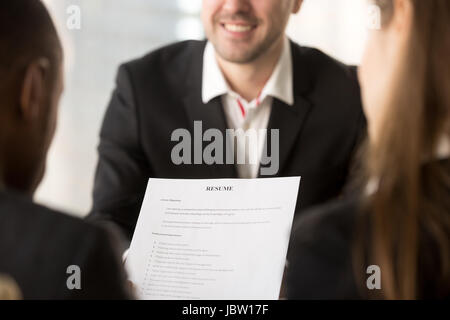 Close up of employers or recruiters holding reviewing cv of happy applicant smiling at background during interview, - Stock Photo