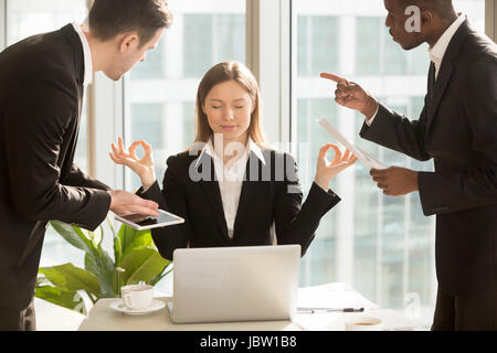 Beautiful businesswoman meditating at workplace, ignoring work, not listening to annoying clients or bothering colleagues - Stock Photo