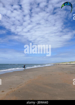CASTRICUM, THE NETHERLANDS - JUNE 10, 2017: Young woman handling her kite while standing on the beach with her surfboard - Stock Photo