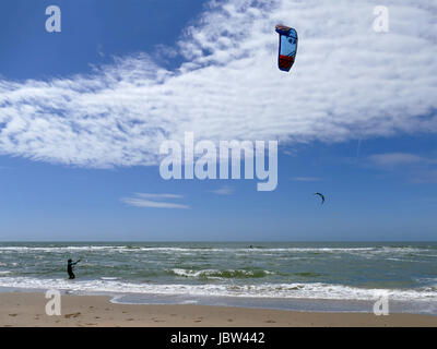 CASTRICUM, THE NETHERLANDS - JUNE 10, 2017: Young woman handling her kite while standing in shallow water with kite - Stock Photo