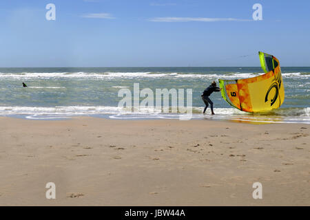 CASTRICUM, THE NETHERLANDS - JUNE 10, 2017: Young woman helping another woman handling her kite while getting out - Stock Photo