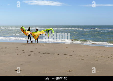 CASTRICUM, THE NETHERLANDS - JUNE 10, 2017: two young women handling a kite while standing on the beach - Stock Photo