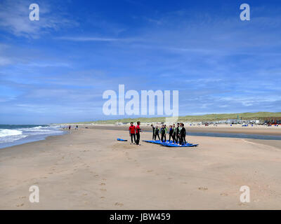 CASTRICUM, THE NETHERLANDS - JUNE 10, 2017: Young teenagers having fun with surfing lessons practising on the beach - Stock Photo