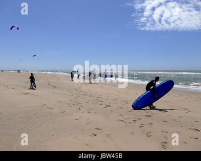 CASTRICUM, THE NETHERLANDS - JUNE 10, 2017: Young teenagers having fun with surfing lessons carrying the surfboards - Stock Photo