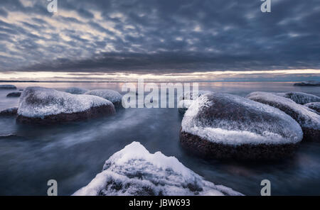 Scenic landscape with sea and sunset at winter time in rocky coastline - Stock Photo