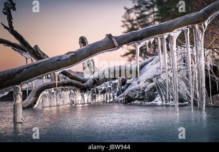 Scenic landscape with icicles and lake at the winter evening - Stock Photo