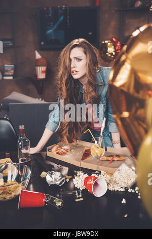 Depressed young woman with hangover leaning at messy table after party - Stock Photo