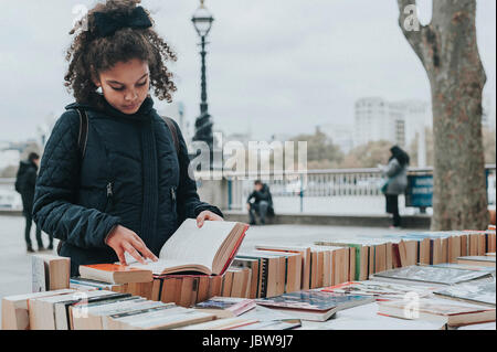 A 10 years old child is browsing second hand books at Southbank Centre Book Market, London. - Stock Photo