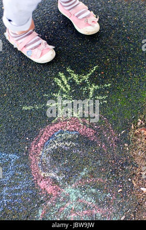 Child is drawing on the playground tarmac with colorful chalks. Cropped to only include her feet. - Stock Photo