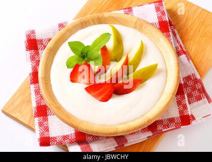 Bowl of semolina pudding served with fresh fruit - Stock Photo