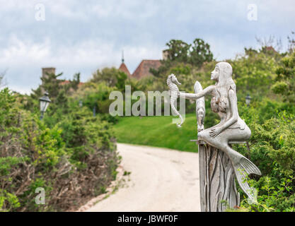 a mermaid looking at a seahorse, part of an elaborate gate to a Long Island Mansion - Stock Photo